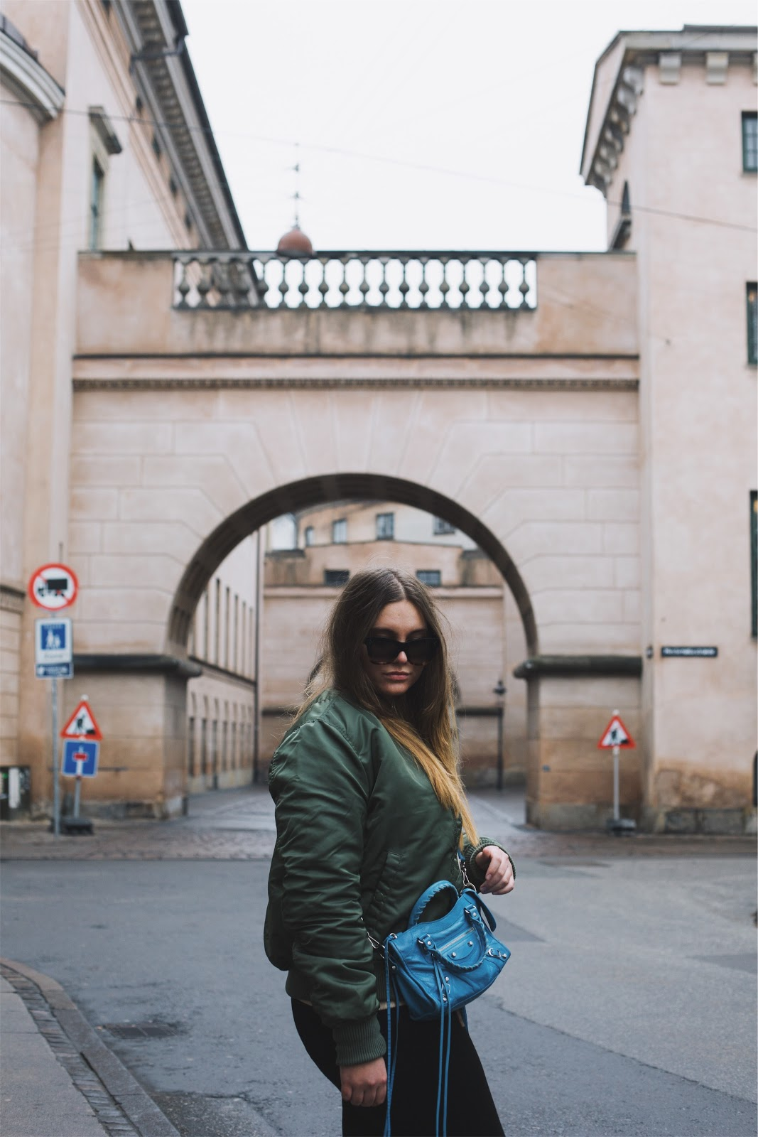 fashion blogger dominique candido wearing alpha industries bomber balenciaga bag celine sunglasses and alexander mcqueen sneakers