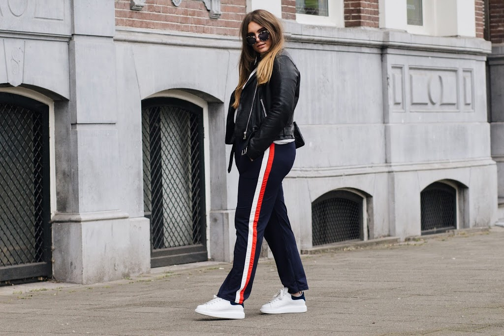 fashion blogger dominique candido wearing a chanel bag ganni trousers yeezlouise t shirt goosecraft leather jacket miu miu sunglasses and alexander mqcueen sneakers